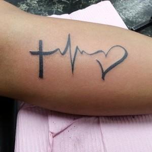 Kreuz Herz Tattoo am Unterarm